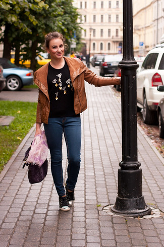 Comment porter: veste motard en cuir tabac, pull à col rond orné noir, jean skinny bleu marine, baskets basses noires