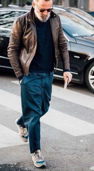 Comment porter: veste motard en cuir marron, pull à col rond noir, pantalon chino bleu marine, chaussures de sport en daim beiges
