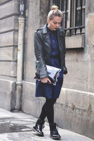 Comment porter: veste motard en cuir noire, robe chemise en denim bleu marine, bottines plates à lacets en cuir noires, pochette en cuir argentée