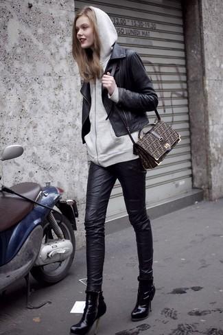 Comment porter: veste motard en cuir noire, sweat à capuche gris, jean skinny en cuir noir, bottines en cuir noires