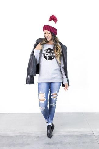 Comment porter: veste motard en cuir noire, sweat-shirt imprimé gris, jean skinny déchiré bleu, bottines en cuir noires