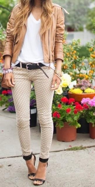 Comment porter: veste motard en cuir marron clair, t-shirt à col en v blanc, jean skinny á pois beige, sandales à talons en cuir noires