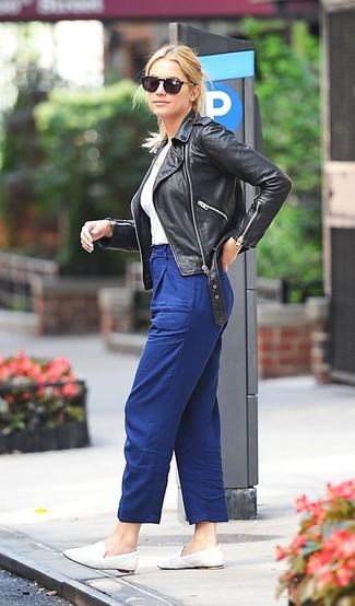 Comment porter des slippers en cuir blancs: Porte une veste motard en cuir noire et un pantalon carotte bleu pour achever un style chic et glamour. Rehausse cet ensemble avec une paire de des slippers en cuir blancs.