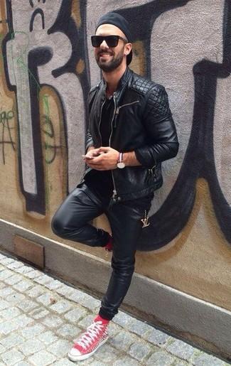Comment porter: veste motard en cuir matelassée noire, t-shirt à col rond noir, pantalon de jogging en cuir noir, baskets montantes rouges