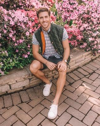 Comment porter: veste sans manches matelassée olive, chemise à manches courtes à carreaux multicolore, short gris foncé, baskets basses en toile blanches
