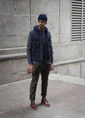 Comment porter: veste sans manches bleu marine, chemise à manches longues imprimée bleu marine, pantalon chino olive, bottes de travail en cuir marron foncé