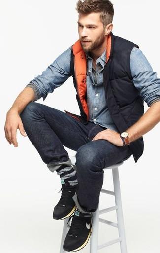 Comment porter: veste sans manches matelassée noire, chemise en jean bleu clair, t-shirt à manche longue et col boutonné gris, jean gris foncé