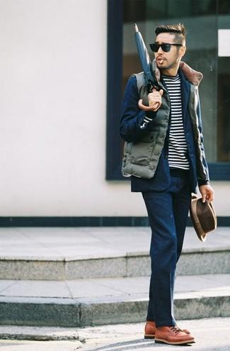 Comment porter: veste sans manches matelassée olive, costume bleu marine, pull à col rond à rayures horizontales noir et blanc, bottes de loisirs en cuir tabac