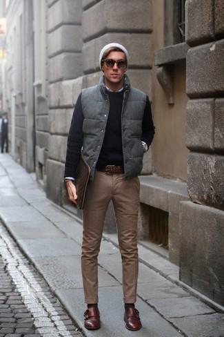 Comment porter: veste sans manches matelassée grise, pull à col rond noir, chemise à manches longues blanche, pantalon chino marron