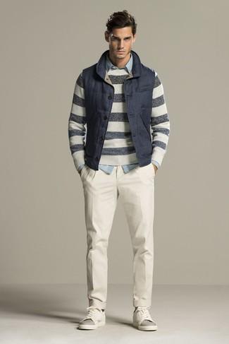 Comment porter: veste sans manches matelassée bleu marine, pull à col rond à rayures horizontales gris, chemise en jean bleu clair, pantalon de costume blanc