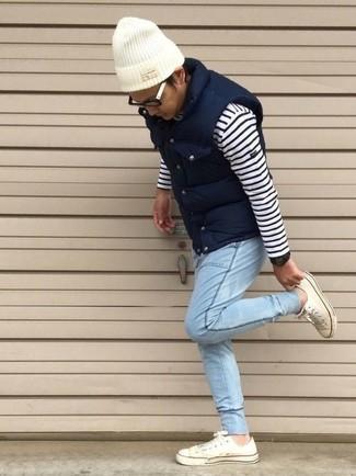 Comment porter: veste sans manches matelassée bleu marine, pull à col rond à rayures horizontales blanc et bleu marine, jean bleu clair, baskets basses blanches