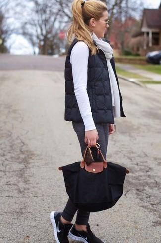 Comment porter: veste sans manches matelassée noire, pull à col rond blanc, leggings gris foncé, chaussures de sport noires