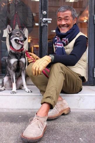 Comment porter: veste sans manches matelassée beige, pull à col rond bleu marine, pantalon chino olive, bottines chukka en daim beiges