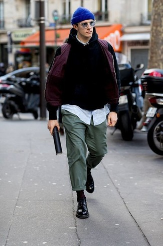 Porte une veste sans manches pourpre et un pantalon chino vert foncé pour obtenir un look relax mais stylé. Fais d'une paire de des chaussures derby en cuir noires ton choix de souliers pour afficher ton expertise vestimentaire.