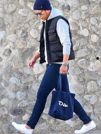 Comment porter: veste sans manches matelassée noire, sweat à capuche gris, jean skinny bleu marine, baskets à enfiler en toile blanches