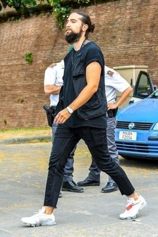 Tendances mode hommes: Marie une veste sans manches noire avec un jean skinny noir pour obtenir un look relax mais stylé. Jouez la carte décontractée pour les chaussures et complète cet ensemble avec une paire de des chaussures de sport blanches.
