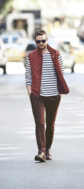 Comment porter: veste sans manches matelassée rouge, t-shirt à manche longue à rayures horizontales blanc et noir, pantalon chino marron, bottes de loisirs en cuir marron foncé
