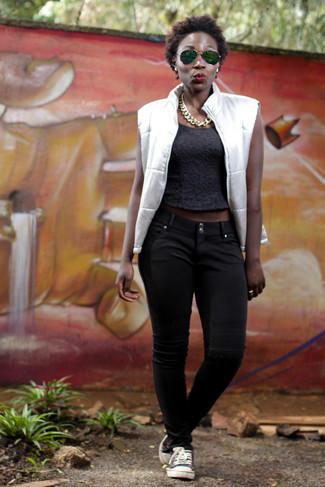 Comment porter une veste sans manches blanche: Associe une veste sans manches blanche avec un pantalon chino noir pour créer un look génial et idéal le week-end. Une paire de des baskets basses noires et blanches est une option astucieux pour complèter cette tenue.