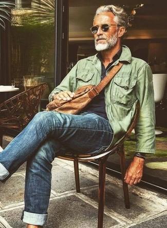 Comment porter: veste style militaire olive, chemise à manches longues bleu marine, jean bleu, besace en cuir marron