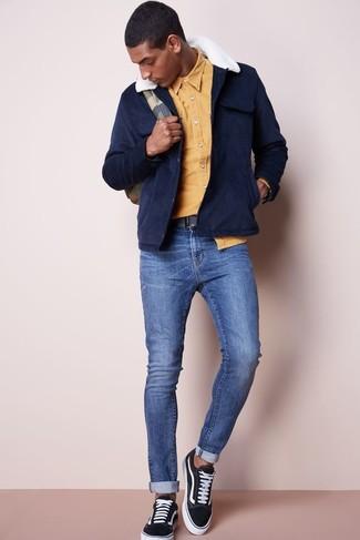 Comment porter: veste style militaire en daim bleu marine, chemise à manches longues jaune, jean skinny bleu, baskets basses en toile noires