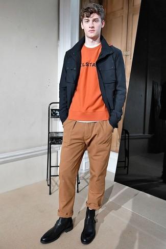 Comment porter: veste style militaire noire, sweat-shirt imprimé orange, t-shirt à col rond blanc, pantalon chino marron clair