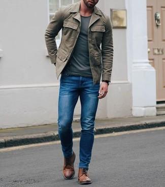 Comment porter: veste style militaire olive, t-shirt à col rond gris foncé, jean skinny bleu, bottes brogue en cuir marron