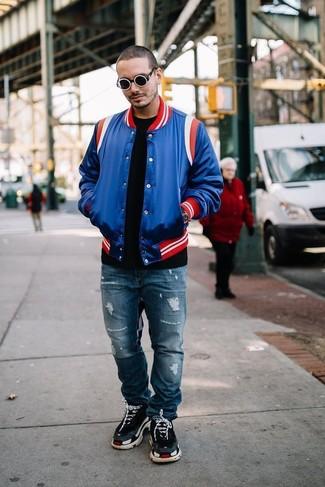 Comment porter: veste universitaire bleue, t-shirt à col rond noir, jean déchiré bleu, chaussures de sport noires