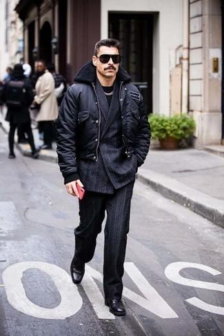 Comment s'habiller après 40 ans: Pense à harmoniser une veste universitaire noire avec un costume à rayures verticales bleu marine pour un look idéal au travail. D'une humeur créatrice? Assortis ta tenue avec une paire de bottines chelsea en cuir noires.