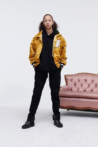 Comment porter: veste universitaire dorée, sweat à capuche noir, pantalon de jogging noir, baskets montantes en daim noires