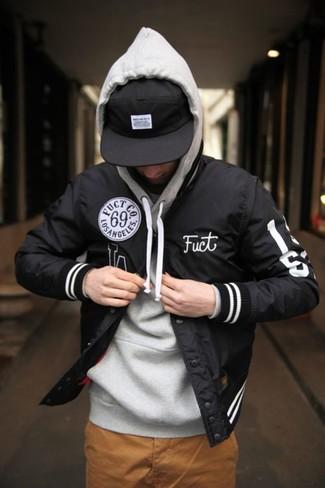 Comment porter: veste universitaire noire, sweat à capuche gris, pantalon chino tabac, casquette de base-ball noire