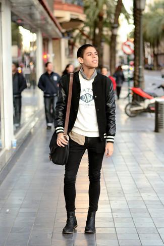 Comment porter: veste universitaire noire, pull à col rond imprimé blanc et noir, chemise à manches longues camouflage marron, jean skinny noir