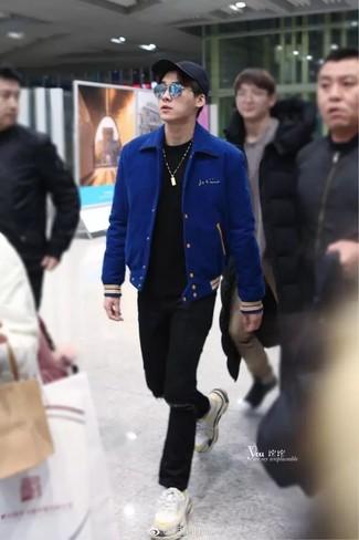 Comment porter: veste universitaire bleue, t-shirt à col rond noir, jean déchiré noir, chaussures de sport blanches