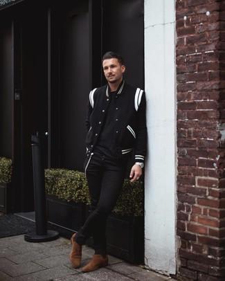 Comment porter: veste universitaire noire et blanche, t-shirt à col rond noir, jean skinny noir, bottines chelsea en daim marron