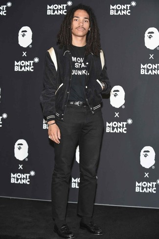 Comment porter: veste universitaire noire et blanche, t-shirt à col rond imprimé noir et blanc, pantalon chino noir, slippers en cuir noirs