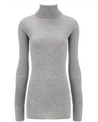 Pense à harmoniser un jean skinny déchiré bleu avec un pull à col roulé pour achever un style chic et glamour.